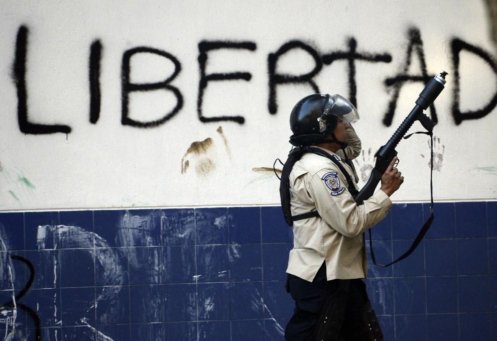 """6.WENEZUELA, Caracas, 22 lutego 2014: Policjant z oddziałów tłumiących zamieszki na tle napisu """"WOLNOŚĆ"""". AFP PHOTO/ JUAN BARRETO"""