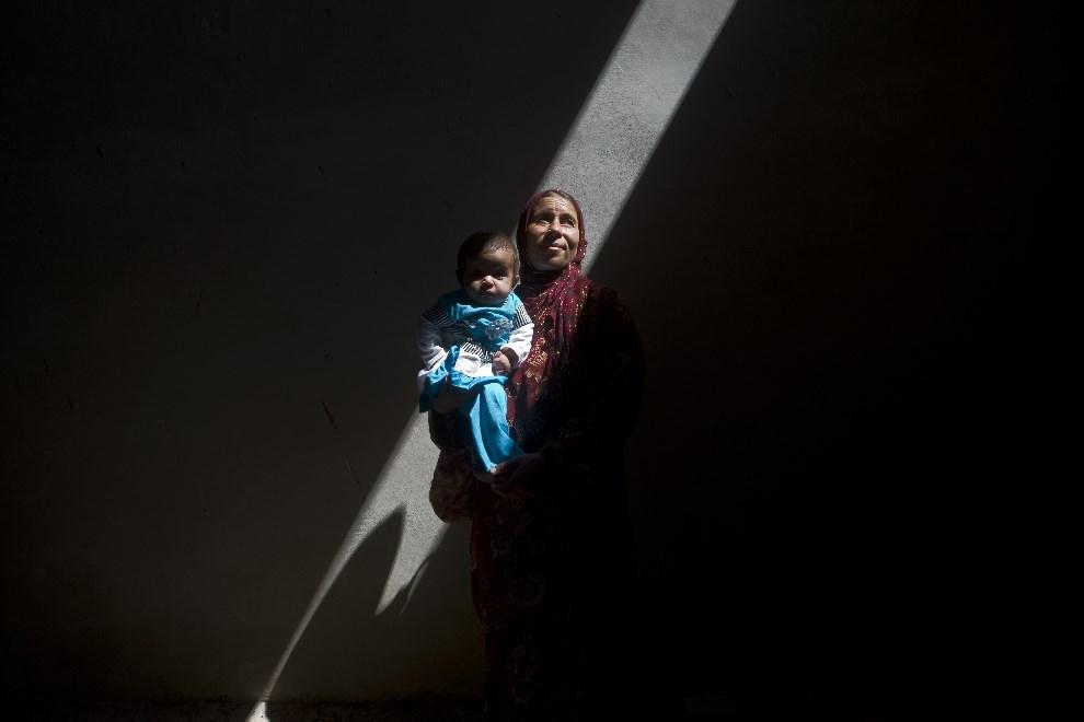 6.SYRIA, Saraqib, 9 września 2013: Kobieta z dzieckiem w opuszczonym budynku. AFP PHOTO / GIOVANNI DIFFIDENTI