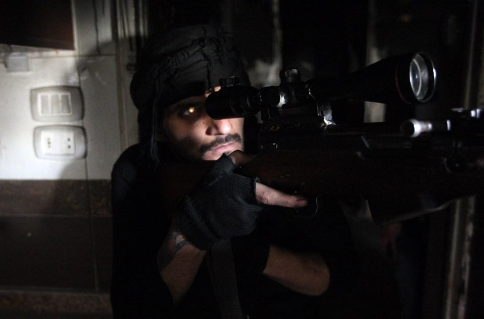 6.SYRIA, Aleppo, 3 marca 2014: Snajper walczący po stronie rebeliantów. AFP PHOTO/AMC/MAHMUD ABDEL RAHMAN