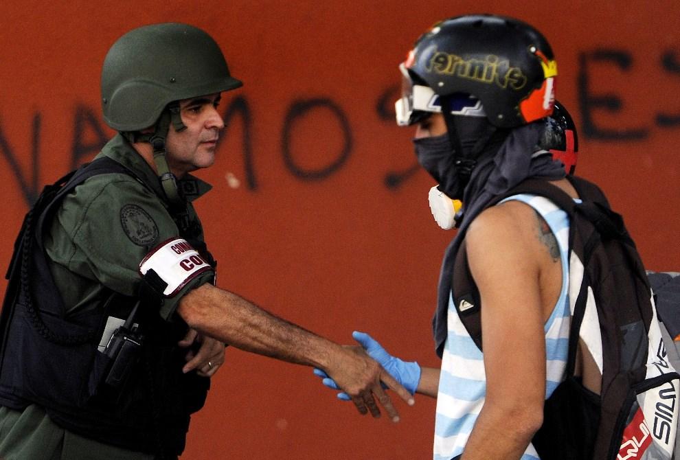 6.WENEZUELA, Caracas, 11 marca 2014: Oficer gwardii narodowej ściska dłoń jednego z uczestników antyrządowego protestu. AFP PHOTO/LEO RAMIREZ