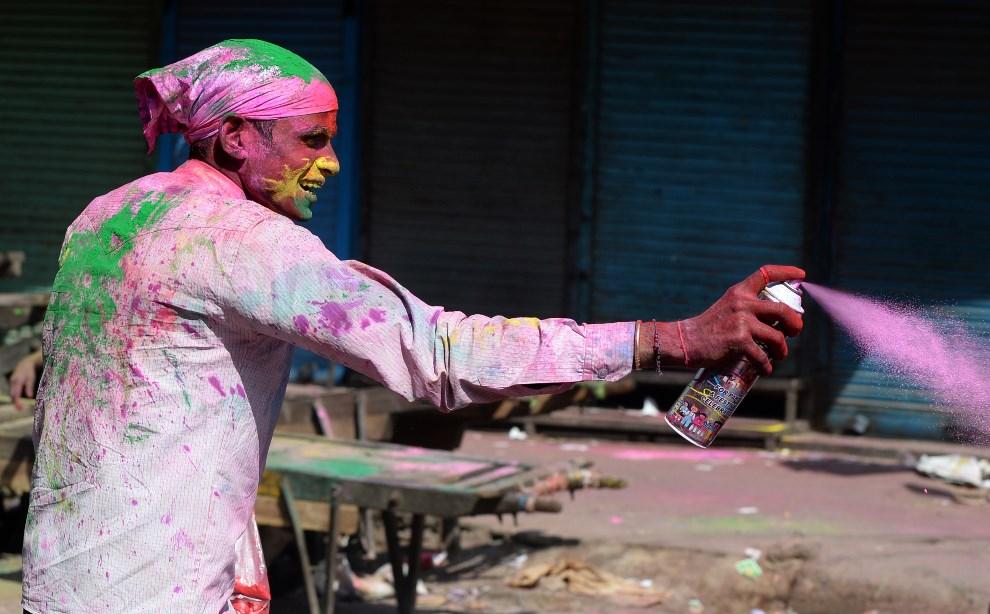 6.INDIE, New Delhi, 17 marca 2014: Mężczyzna spryskuje uczestników zabawy kolorową farbą. AFP PHOTO /SAJJAD HUSSAIN