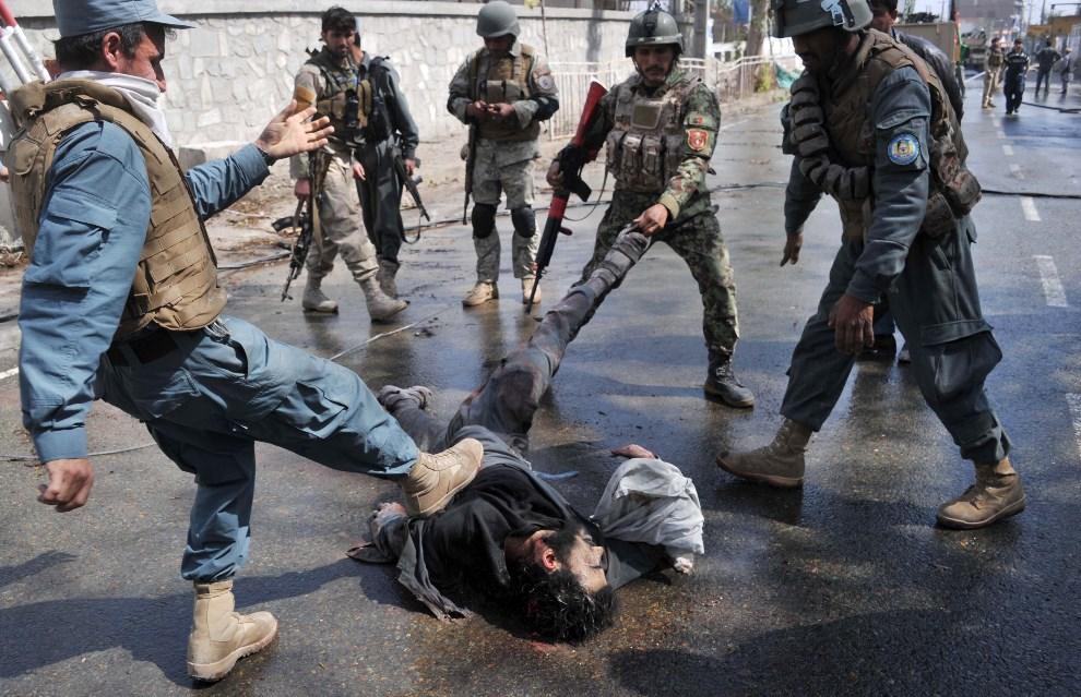 6.AFGANISTAN, Jalalabad, 20 marca 2014: Policjanci ciągnął ciało mężczyzny biorącego udział w zamachu na posterunek policji. AFP PHOTO/Noorullah Shirzada