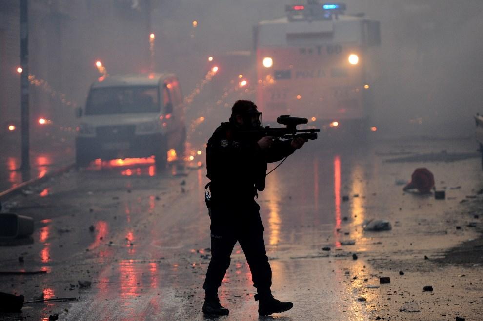 7.TURCJA, Stambuł, 12 marca 2014: Policjant strzelający gumowymi pociskami w kierunku uczestników demonstracji. AFP PHOTO/ OZAN KOSE