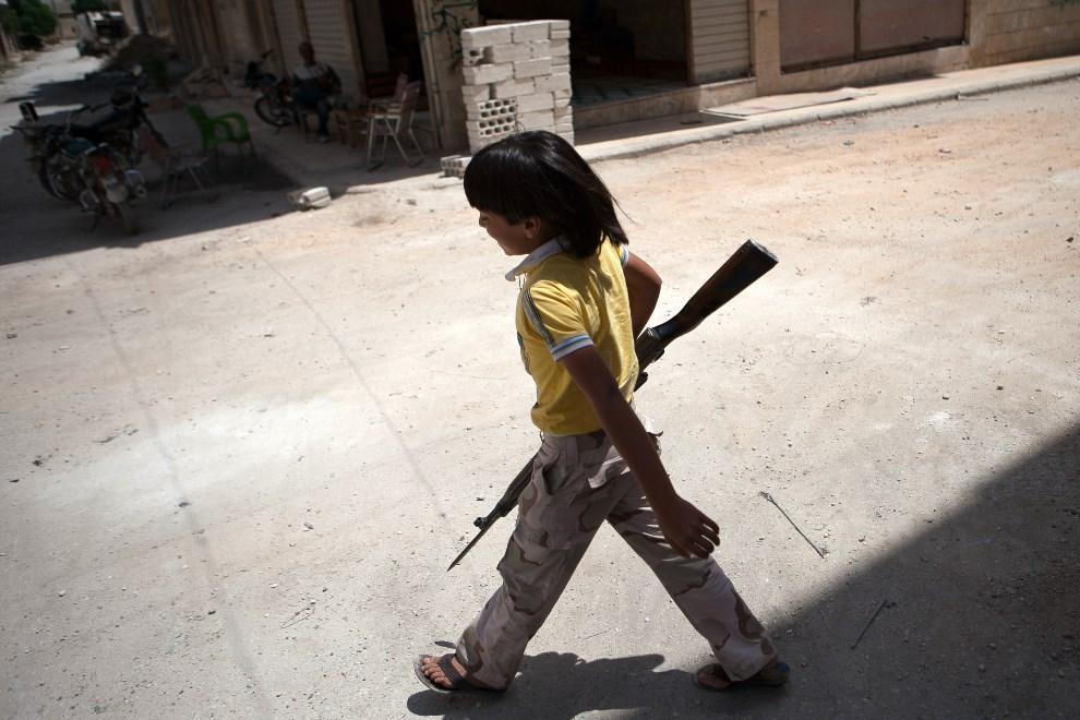 8.SYRIA, Aleppo, 13 czerwca 2013: Chłopiec z karabinem pomagający rebeliantom. AFP PHOTO DANIEL LEAL-OLIVAS