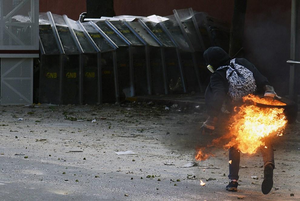9.WENEZUELA, Caracas, 2 marca 2014: Protestujący opozycjonista  rzuca zapaloną oponą w kierunku policjantów. AFP PHOTO / Leo Ramirez