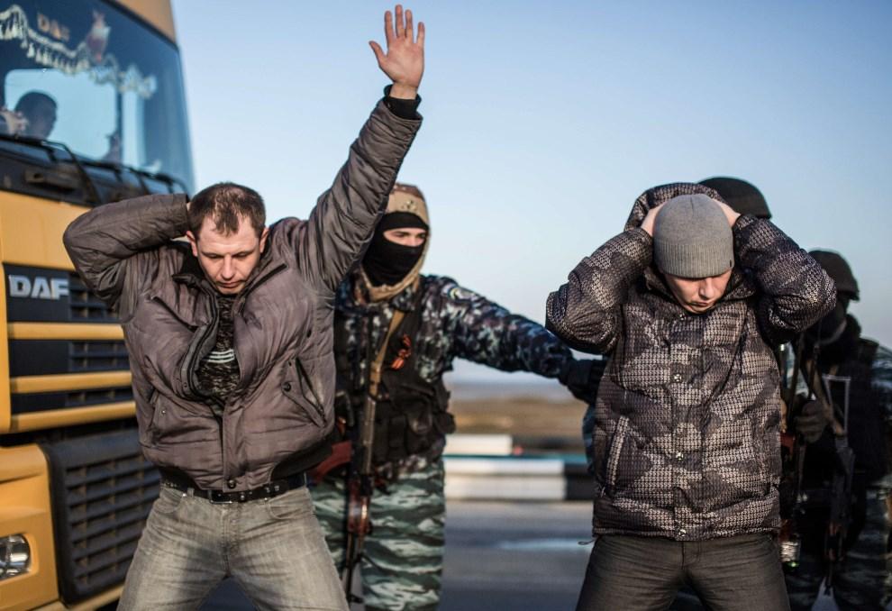 9.UKRAINA, Chongar, 10 marca 2014: Mężczyźni przeszukiwani przez rosyjskich żołnierzy na jednym z punktów kontrolnych. AFP PHOTO/ALISA BOROVIKOVA