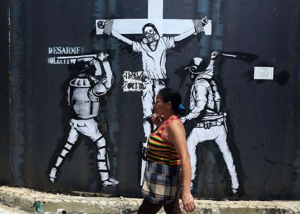 10.WENEZUELA, Caracas, 24 kwietnia 2014: Kobieta mijająca graffiti w centrum miasta. AFP PHOTO/JUAN BARRETO