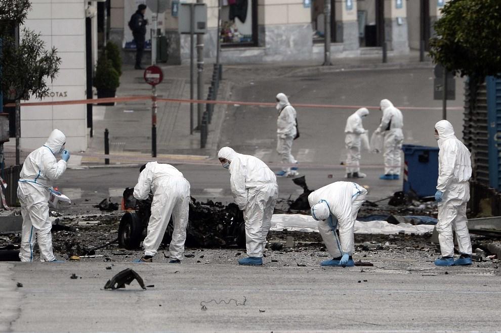 10.GRECJA, Ateny, 10 kwietnia 2014: Policjanci przeszukują wrak samochodu, który eksplodował przed siedzibą banku. AFP PHOTO/ LOUISA GOULIAMAKI