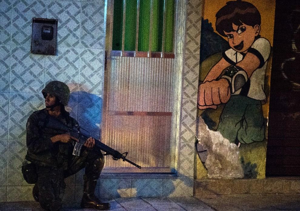 11.BRAZYLIA, Rio de Janeiro, 30 marca 2014: Żołnierz na ulicy w faweli Nueva Holanda. AFP PHOTO/CHRISTOPHE SIMON