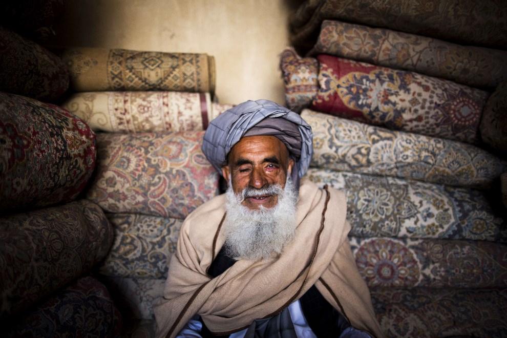 11.AFGANISTAN, Herat, 2 kwietnia 2014: Sprzedawca dywanów importowanych z Iranu. AFP PHOTO/BEHROUZ MEHRI
