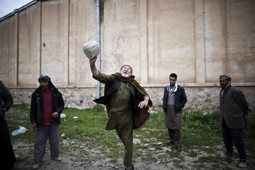 12.AFGANISTAN, Herat, 3 kwietnia 2014: Pracownicy komisji wyborczej rzucają kamieniami w oczekiwaniu na załadowanie na samochody urn wyborczych. AFP PHOTO/BEHROUZ   MEHRI