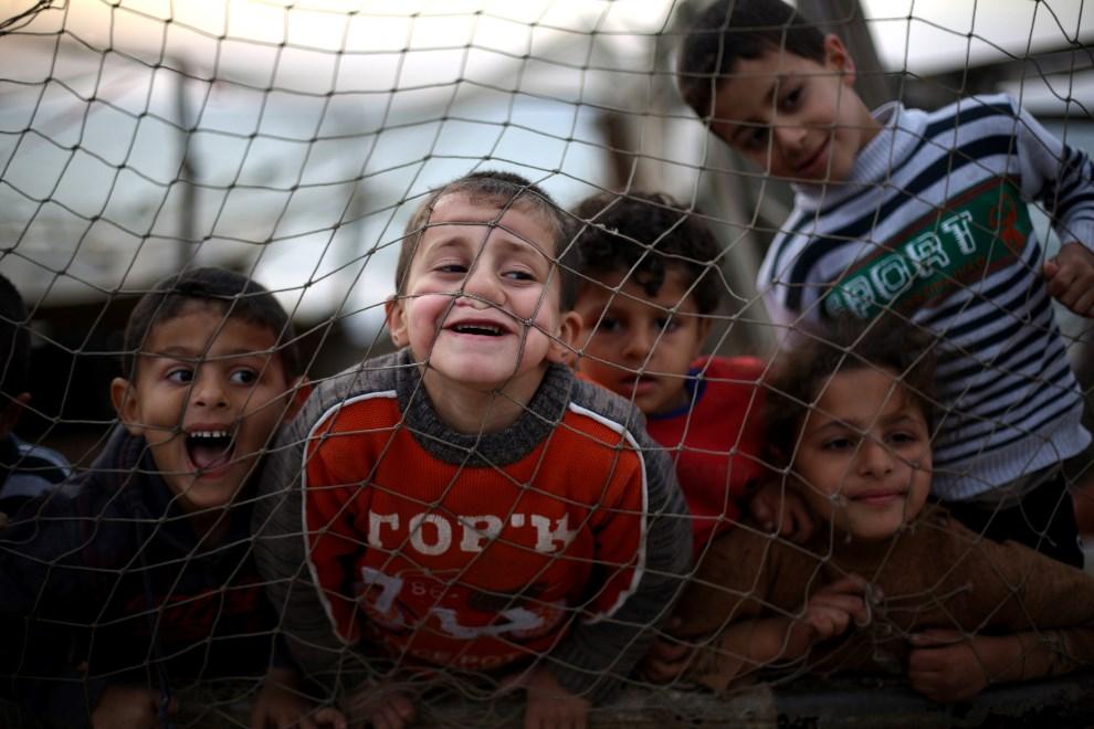 12.STREFA GAZY, 13 kwietnia 2014: Palestyńskie dzieci bawią się w obozie dla uchodźców. AFP PHOTO/MOHAMMED ABED