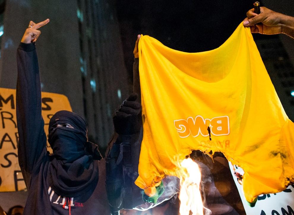 12.BRAZYLIA, Rio de Janeiro, 27 marca 2014: Protestujący przeciw organizacji finałów FIFA w Rio, palą koszulkę reprezentacji Brazylii. (Foto: Buda Mendes/Getty   Images)