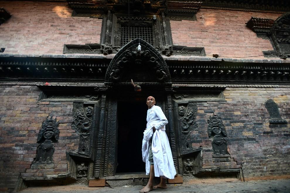 13.NEPAL, Bhaktaour, 10 kwietnia 2014: Kapłan wchodzący do świątyni przed uroczystościami związanymi z obchodami nowego roku. AFP PHOTO/ Prakash MATHEMA