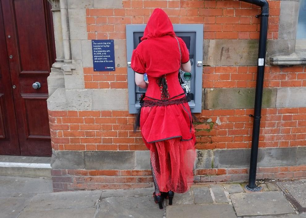 13.WIELKA BRYTANIA, Whitby, 26 kwietnia 2014: Kobieta w stroju przypominającym Czerwonego Kapturka, wypłaca pieniądze z bankomatu. (Foto: Ian Forsyth/Getty Images)