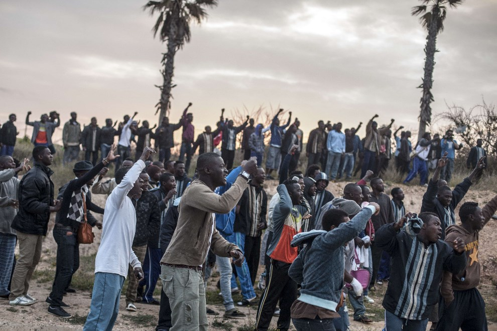 14.MAROKO, Beni Enza, 28 marca 2014: Osoby przebywające w ośrodku dla uchodźców dopingują grupę przedzierającą się przez ogrodzenie na terytorium Hiszpanii. AFP   PHOTO/ JOSE COLON