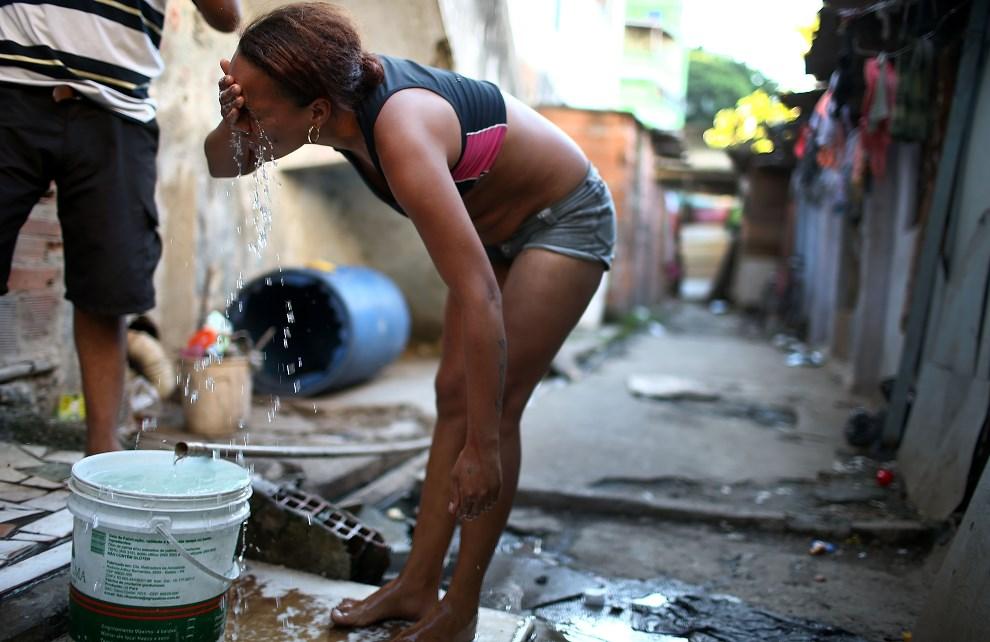 16.BRAZYLIA, Rio de Janeiro, 18 marca 2014: Mieszkanka faweli obmywa twarz w ogólnodostępnym ujęciu wody. (Foto: Mario Tama/Getty Images)