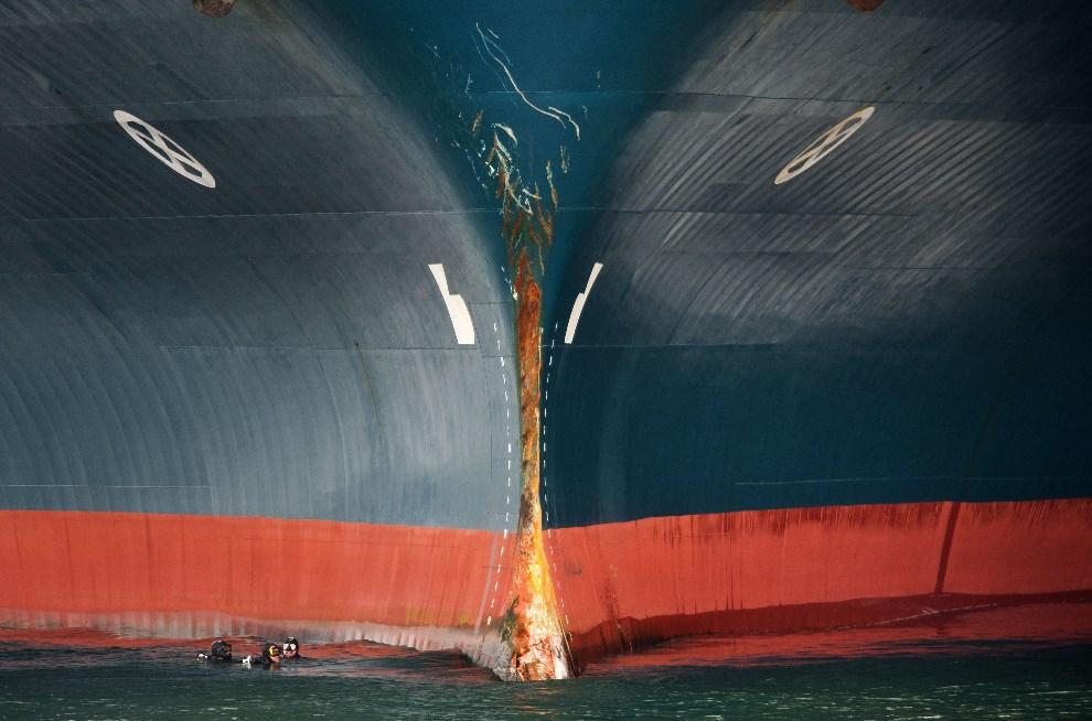 """16.HISZPANIA, Vigo, 1 kwietnia 2014: Nurkowie sprawdzają kadłub uszkodzonej jednostki """"Baltic Breeze"""", która zderzyła się z kutrem rybackim. AFP PHOTO / MIGUEL   RIOPA"""