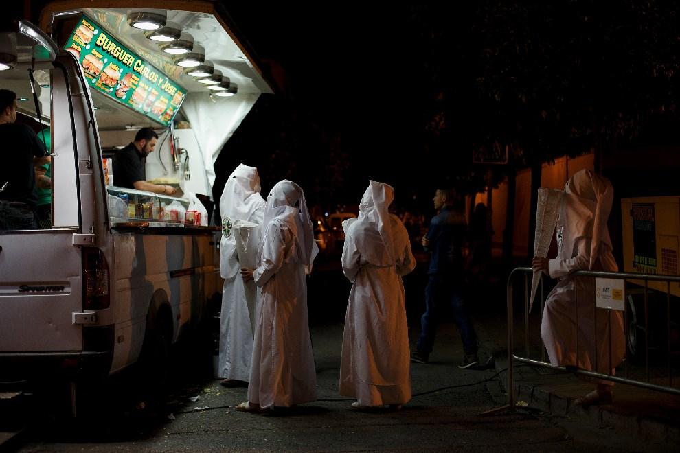 """17.HISZPANIA, Sewilla, 15 kwietnia 2014: Członkowie bractwa """"San Gonzalo"""" kupują jedzenie w ulicznej budce. (Foto: Pablo Blazquez Dominguez/Getty Images)"""