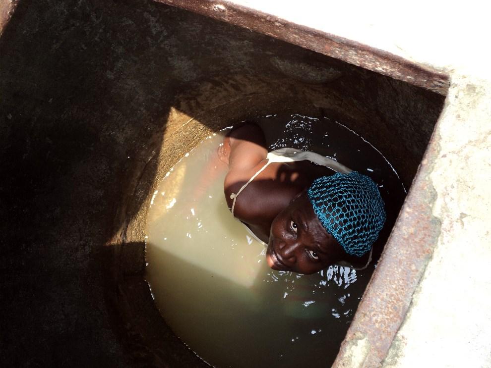 17.NIGERIA, Igbogbo, 15 marca 2014: Kobieta w wykopanej własnoręcznie studni. AFP PHOTO / ADEROGBA OBISESAN