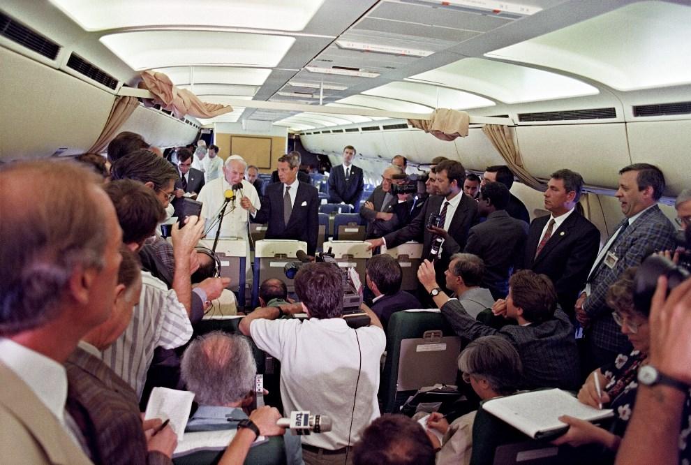 18.NA POKŁADZIE SAMOLTU, 12 września 1990: Jan Paweł II rozmawia z dziennikarzami podczas lotu do Tanzanii. AFP