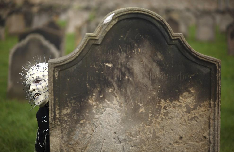 19.WIELKA BRYTANIA, Whitby, 28 kwietnia 2014: Uczestnik gotyckiego weekendu wygląda zza cmentarnego nagrobka. (Foto: Christopher Furlong/Getty Images)
