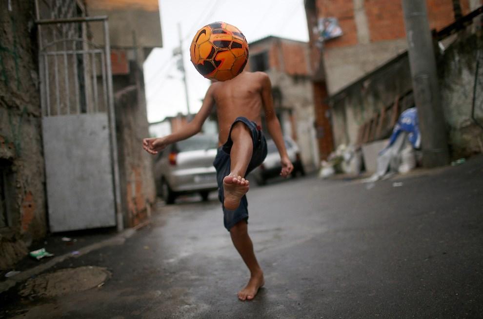 1.BRAZYLIA, Rio de Janeiro, 23 marca 2014: Chłopiec ze spacyfikowanje faweli Complexo do Alemao. (Foto: Mario Tama/Getty Images)