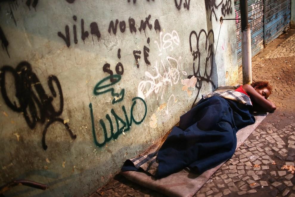 21.BRAZYLIA, Rio de Janeiro, 30 marca 2014: Kobieta śpiąca na ulicy w związku z planowaną likwidacją faweli w której mieszka. (Foto: Mario Tama/Getty Images)