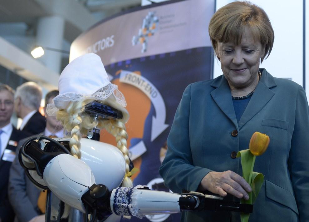 21.NIEMCY, Hanower, 7 kwietnia 2014: Kanclerz Angela Merkel odbiera kwiaty od robota. AFP PHOTO / JOHANNES EISELE