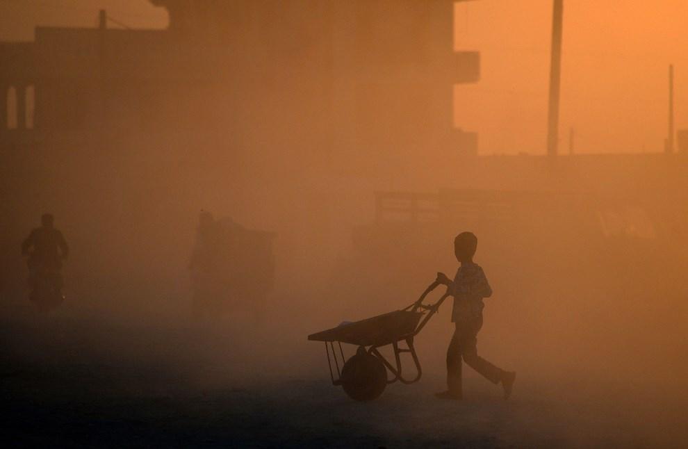 22.AFGANISTAN, Mazar-i-Sharif, 22 kwietnia 2014: Chłopiec z taczką na ulicy w Mazar-i-Sharif. AFP PHOTO/FARSHAD USYAN