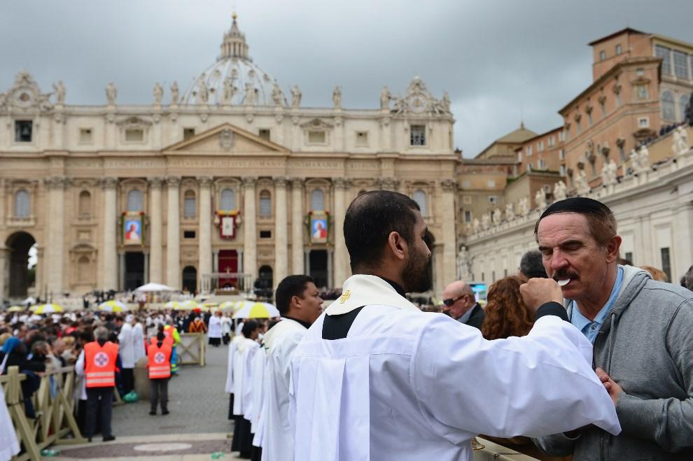 25.WATYKAN, 27 kwietnia 2014: Wierni przyjmujący komunię podczas mszy kanonizacyjnej. (Foto: Jeff J Mitchell/Getty Images)