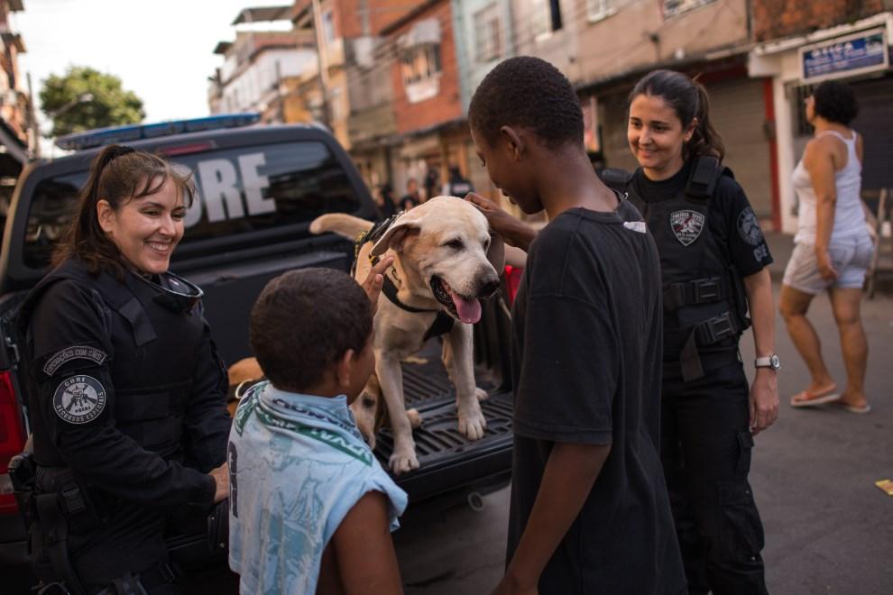 26.BRAZYLIA, Rio de Janeiro, 30 marca 2014: Dzieci bawią się z policyjnym psem. (Foto: Buda Mendes/Getty Images)