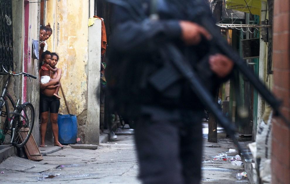 28.BRAZYLIA, Rio de Janeiro, 30 marca 2014: Mieszkańcy faweli Complexo da Mare przyglądają się funkcjonariuszom. (Foto: Mario Tama/Getty Images)