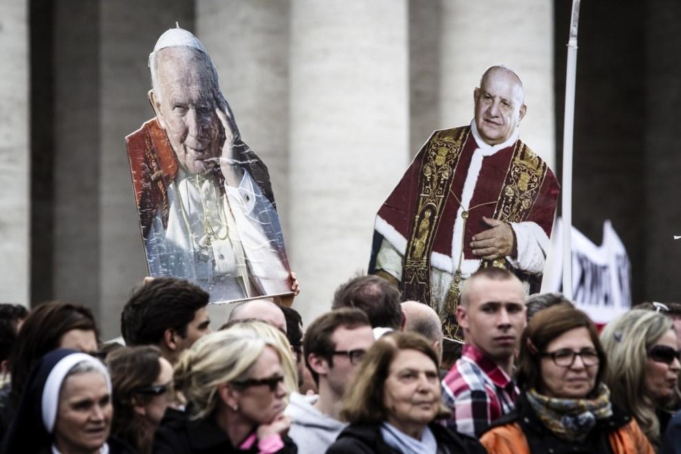 28.WATYKAN, 27 kwietnia 2014: Pielgrzymi na Placu Świętego Piotra trzymają podobizny Jana XXIII i Jana Pawła II. EPA/ANGELO CARCONI Dostawca: PAP/EPA.