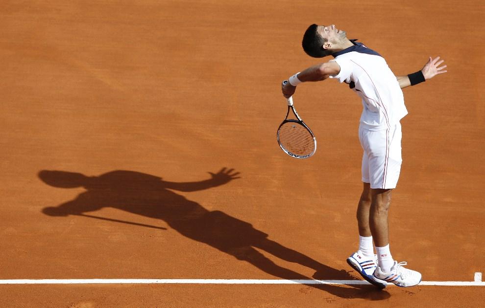 29.MONAKO, 17 kwietnia 2014: Novak Djokovic serwuje piłkę podczas pojedynku z Pablo Carreno Busta. AFP PHOTO / VALERY HACHE