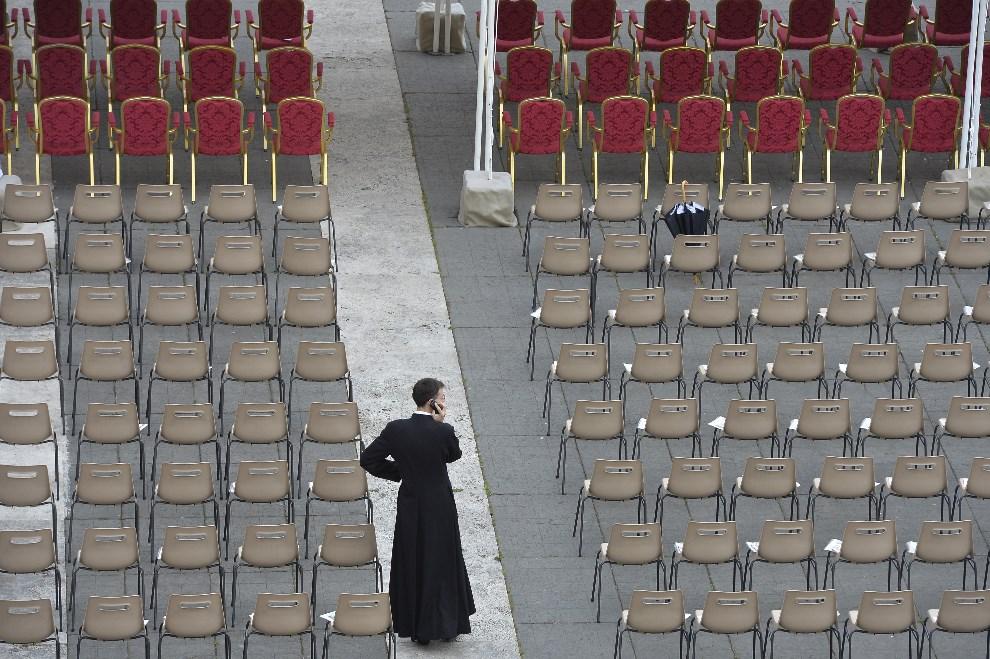 2.WATYKAN, 27 kwietnia 2014: Kapłan nadzorujący kwestie organizacyjne uroczystości. AFP PHOTO / ANDREAS SOLARO
