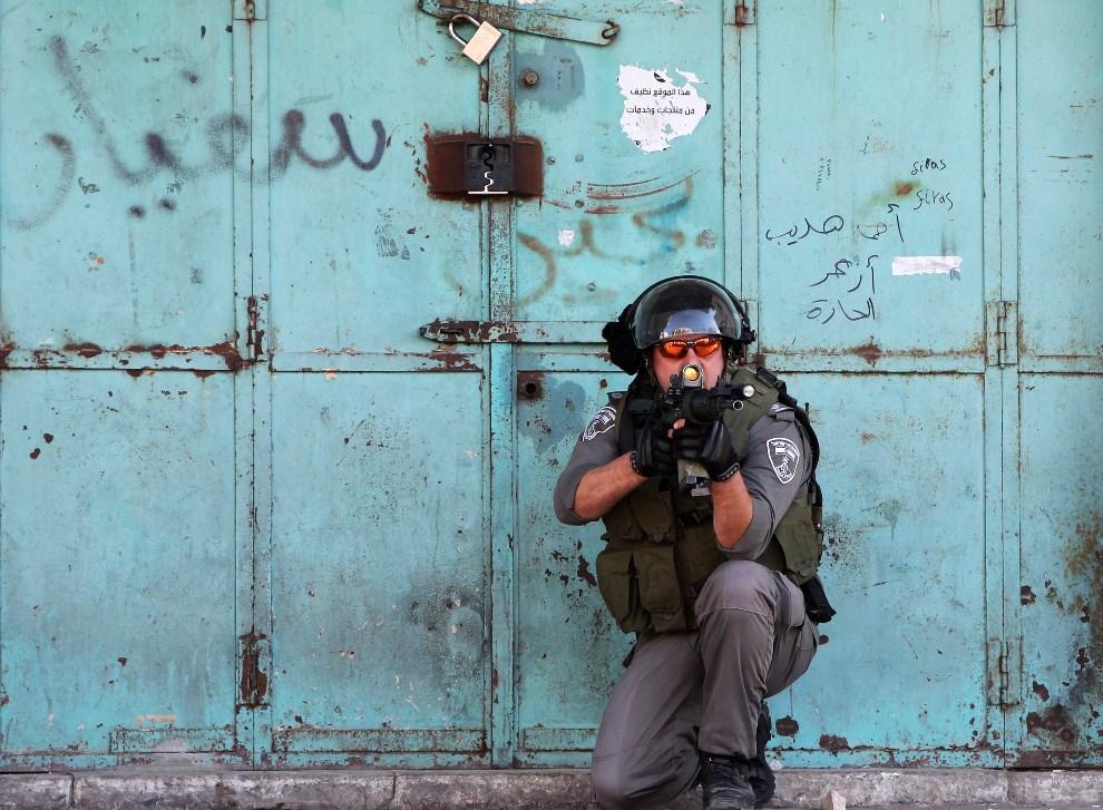 2.ZACHODNI BRZEG, Hebron, 11 kwietnia 2014: Izraelski żołnierz celujący w kierunku Palestyńczyków rzucających kamieniami. AFP PHOTO/ HAZEM BADER