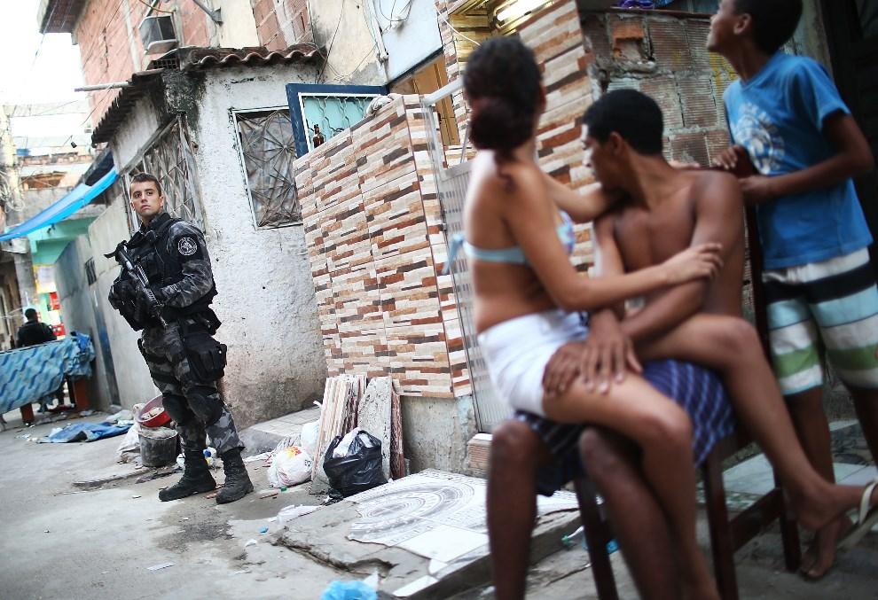 2.BRAZYLIA, Rio de Janeiro, 30 marca 2014: Policjant na pozycji po wejściu jego oddziału do faweli. (Foto: Mario Tama/Getty Images)
