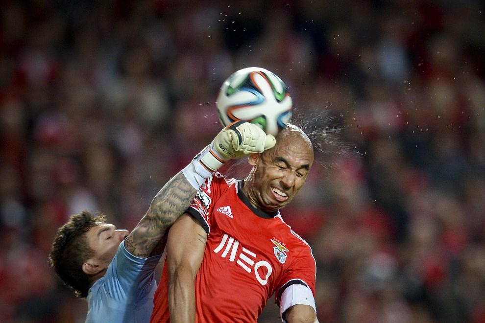 32.PORTUGALIA, Lizbona, 7 kwietnia 2014: Ederson Moraes (po lewej) piąstkuje piłkę podczas meczu  pomiędzy zespołami Benfica i Rio Ave. AFP PHOTO/PATRICIA DE MELO   MOREIRA