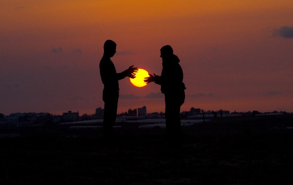 36.STREFA GAZY, 9 kwietnia 2014: Palestyńczycy na tle zachodzącego słońca. AFP PHOTO / DAMIEN MEYER