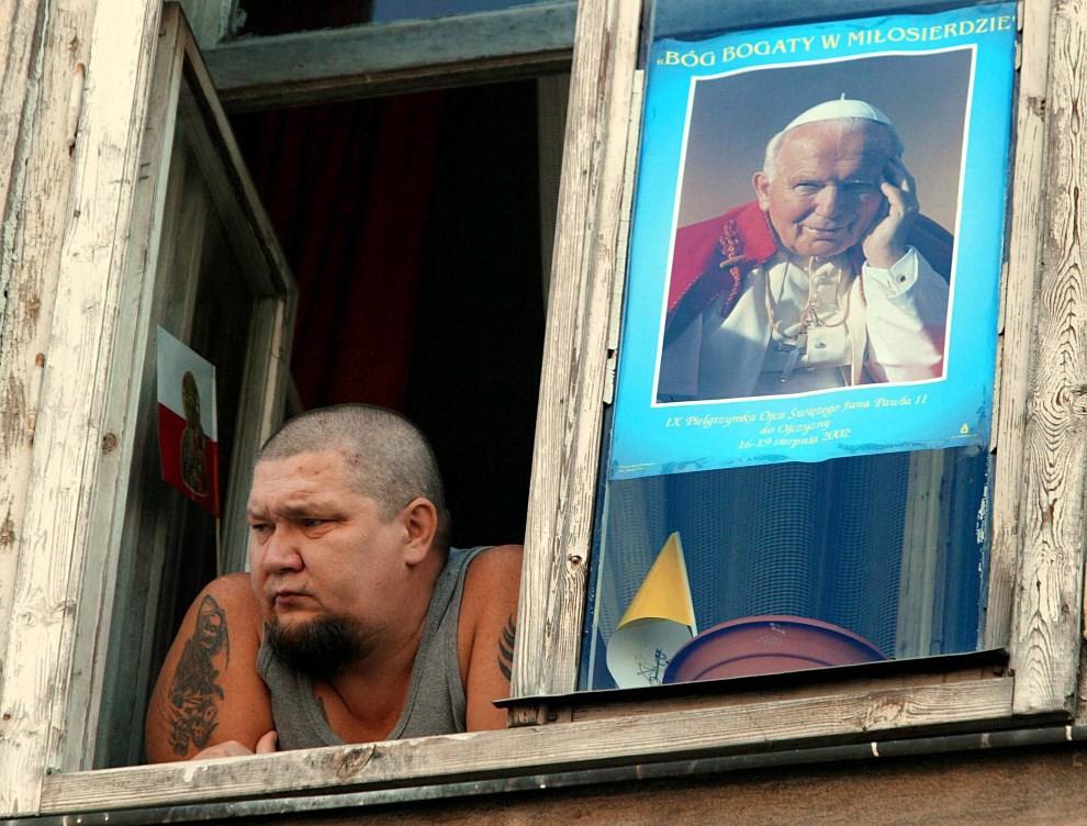 39.POLSKA, Kraków, 17 sierpnia 2002: Mężczyzna w oknie na trasie przejazdu papamobile. AFP PHOTO POOL Vincenzo Pinto