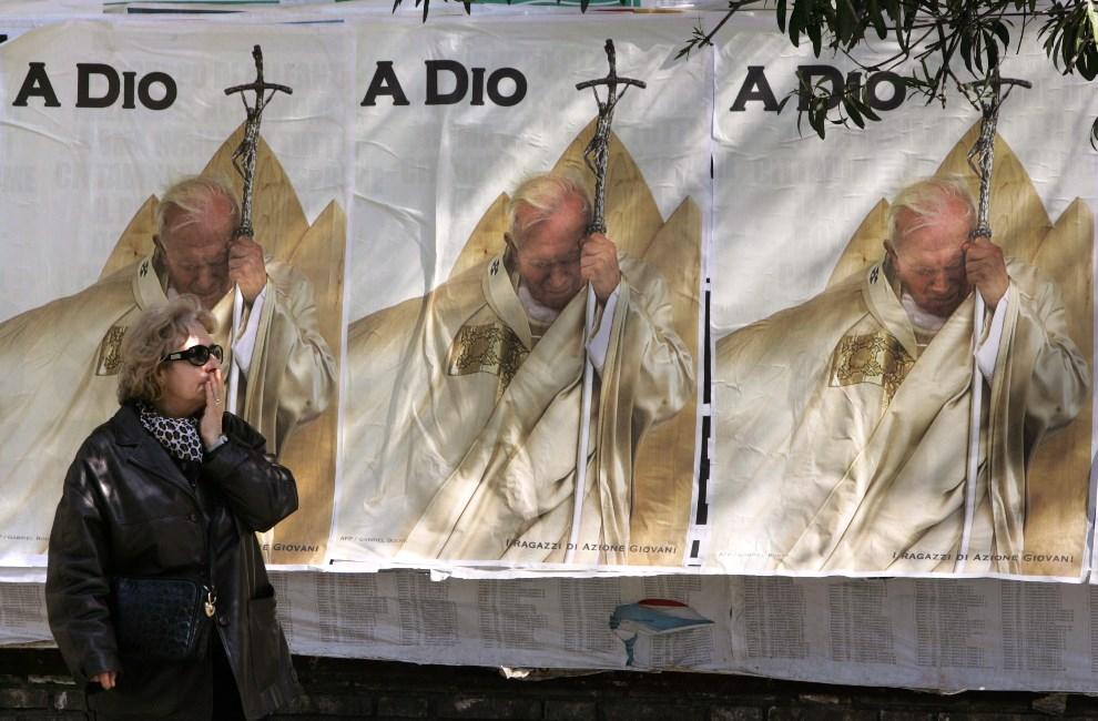46.WŁOCHY, Rzym, 7 kwietnia 2005: Kobieta mija plakaty z wizerunkiem Jana Pawła II.  AFP