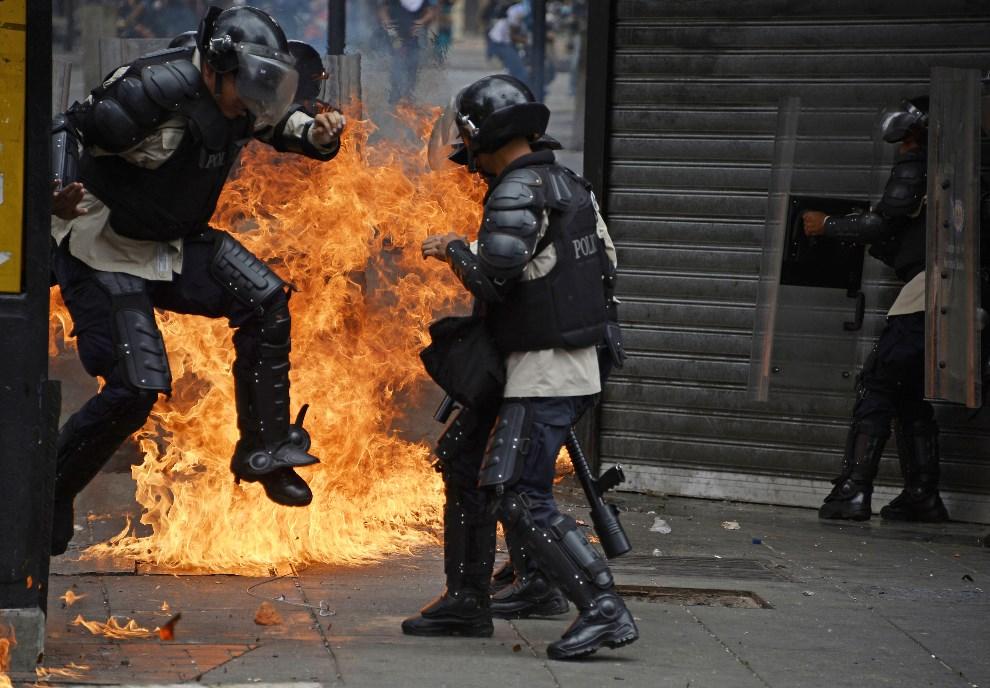 4.WENEZUELA, Caracas, 17 kwietnia 2014: Żołnierze uciekają przed rzuconą butelką z koktajlem Mołotowa. AFP PHOTO/JUAN BARRETO