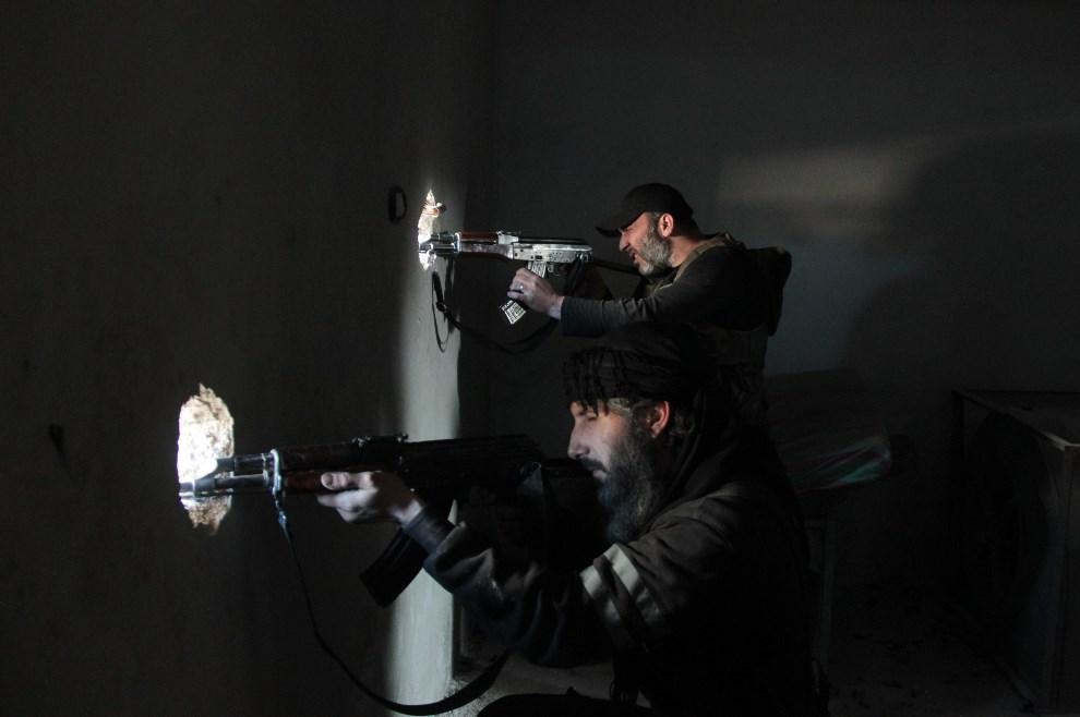 4.SYRIA, Aleppo, 11 kwietnia 2014: Rebelianci obserwują okolicę podczas walk wmieście. AFP PHOTO / MEDO HALAB