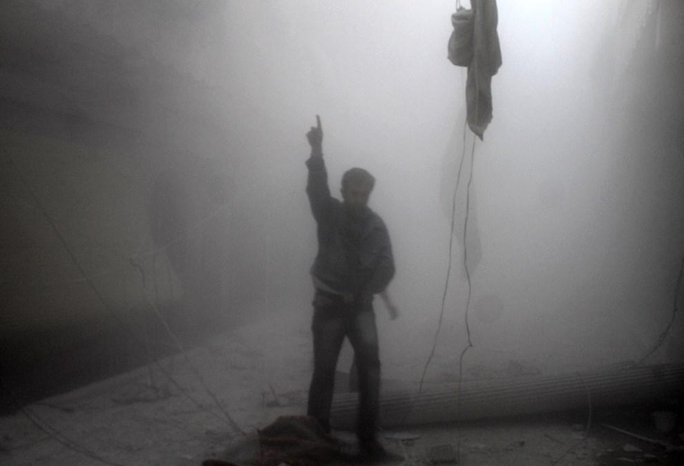 5.SYRIA, Aleppo, 15 kwietnia 2014: Gestykulujący mężczyzna w chwilę po nalocie sił rządowych. AFP PHOTO / BARAA AL-HALABI