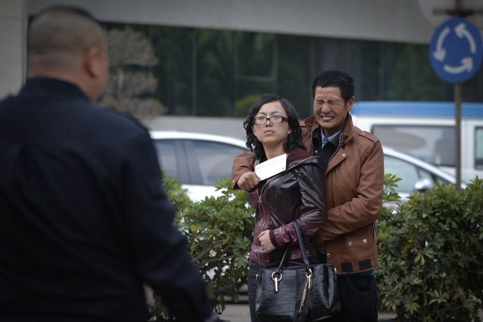 5.CHINY, Kunming , 8 kwietnia 2014: Mężczyzna przetrzymujący zakładniczkę podczas negocjacji z policjantami. AFP PHOTO/AHMAD GHARABLI