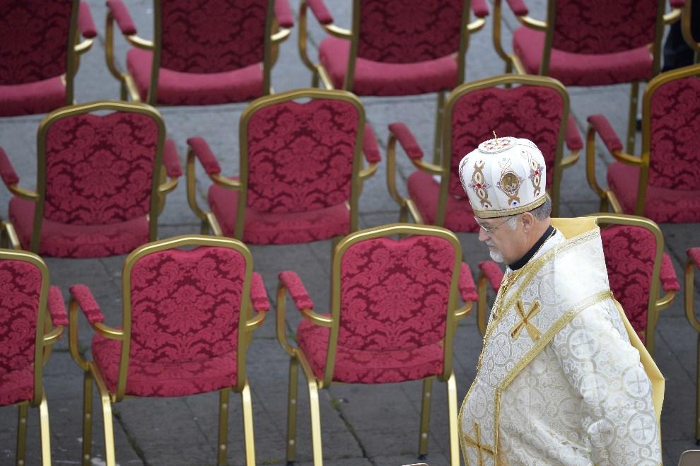 6.WATYKAN, 27 kwietnia 2014: jeden z duchownych zajmuje miejsce przy ołtarzu przed rozpoczęciem mszy kanonizacyjnej. AFP PHOTO / ANDREAS SOLARO