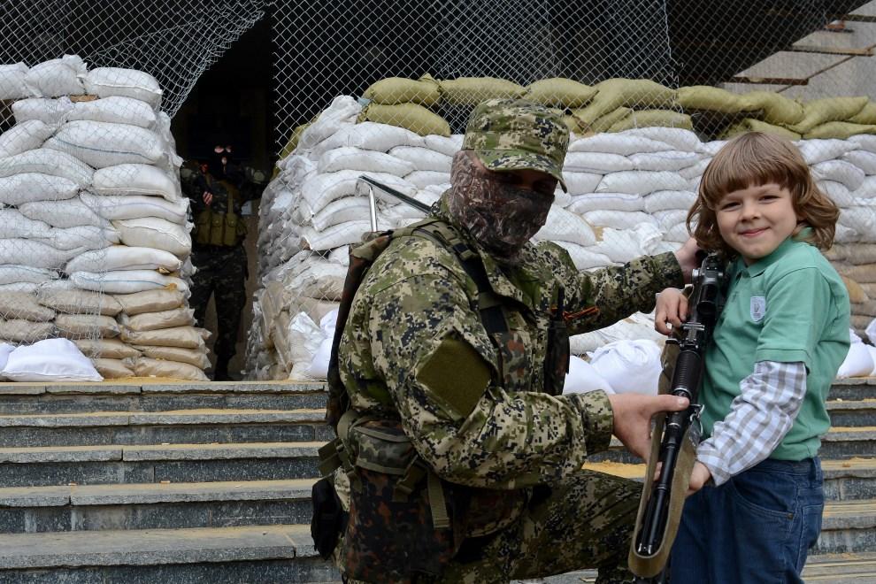 6.UKRAINA, Sławiańsk, 20 kwietnia 2014: Chłopiec w towarzystwie mężczyzny w mundurze bez oznaczeń, przed wejściem do budynku administracji publicznej. AFP PHOTO   / KIRILL KUDRYAVTSEV