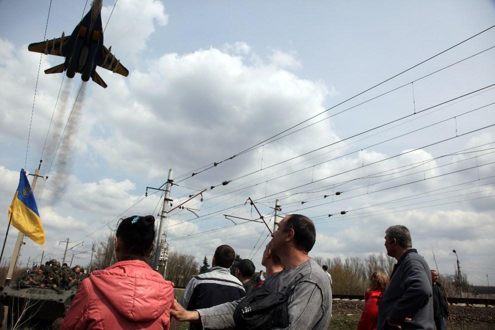 6.UKRAINA, Kramatorsk, 16 kwietnia 2014: Ukraiński MIG 295 przelatuje nad zwolennikami połączenia z Rosją. AFP PHOTO / ANATOLIY STEPANOV