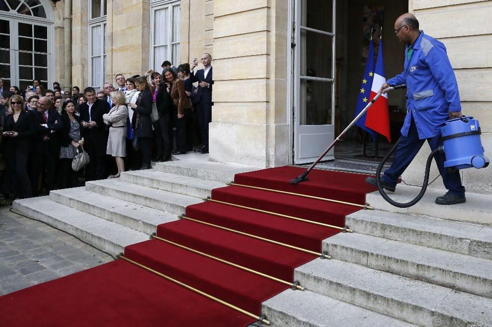 6.FRANCJA, Paryż, 1 kwietnia 2014: Mężczyzna odkurza dywan przed wejściem do siedziby premiera. AFP PHOTO / PATRICK KOVARIK